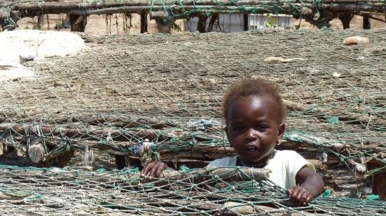 Enfant dans les étalages de séchage de poissons