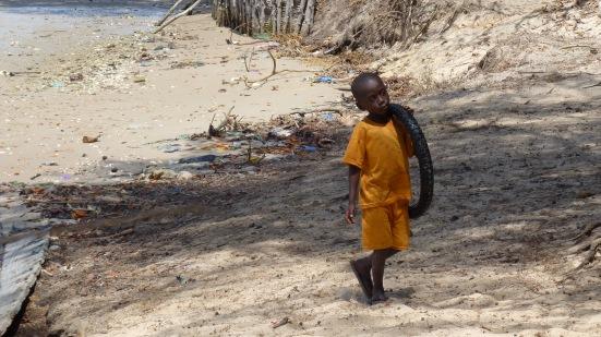 Enfant sur la plage jouant avec une chambre à air